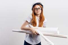 Young beautiful woman in a helmet holds blueprints on white  background, engineer, builder Stock Photo