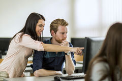 Young beautiful woman helping classmate understand Royalty Free Stock Photo