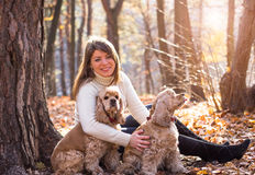 Young beautiful woman and her dog (American Cocker. Spaniel) posing outside at fall time Royalty Free Stock Photos