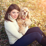 Young beautiful woman and her dog (American Cocker. Spaniel) posing outside at fall time Stock Image