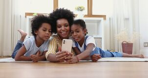 Mother and children having fun using application on cell phone