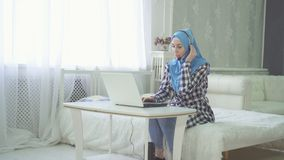 Beautiful woman in hijab at the computer at home with a headset, remote work on stock photo
