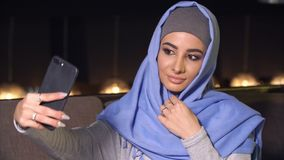 Young beautiful woman in hijab doing selfie on mobile phone camera. Muslim woman and modern technology. Young beautiful woman in hijab doing selfie on mobile Stock Images