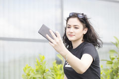 Young beautiful woman, hipster, holding a cell phone in hand and Royalty Free Stock Photo