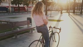 Pretty girl on her urban vintage bicycle at sunset stock footage