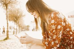 Young beautiful woman hipster using smartphone at the sunny beach. Summer beach travel concept. royalty free stock photos