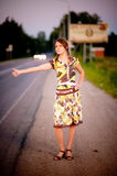 Young beautiful woman hitchhike. Against evening city street Royalty Free Stock Images