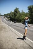 Young beautiful woman hitchhiking along a road Royalty Free Stock Photo
