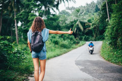 Young beautiful woman hitchhiking standing on road. Back view Royalty Free Stock Photo
