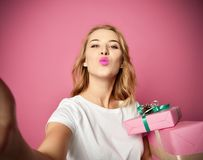 Young beautiful woman hold christmas present gifts smiling and make selfie photo with her cellphone mobile royalty free stock images