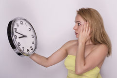 Young beautiful woman holding big clock. time concept. Stock Images