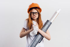 Young beautiful woman holding blueprints and crumpled paper, engineer, building.  Stock Photo