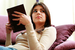 Young beautiful woman holding a book and looking away Royalty Free Stock Image