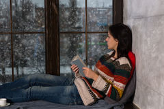 Young beautiful woman holding a book, lying on the windowsill an Royalty Free Stock Images