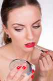 Young beautiful woman holding a brush and coloring her lips. Closeup portrait of young beautiful woman holding a brush and coloring her lips Royalty Free Stock Photography