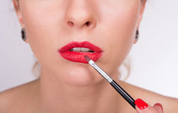 Young beautiful woman holding a brush and coloring her lips. Closeup portrait of young beautiful woman holding a brush and coloring her lips Royalty Free Stock Photos