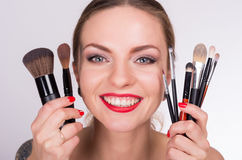 Young beautiful woman holding a brushes near her face Stock Images