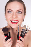 Young beautiful woman holding a brushes under her face Stock Photo