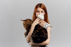 Young beautiful woman holding a cat on a gray background, allergic to pets Stock Photography