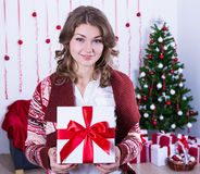 Young beautiful woman holding christmas present box in decorated Stock Photography