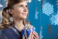 Young beautiful woman holding Christmas present smiling. Royalty Free Stock Photos