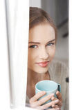 Young beautiful woman holding a cup and looking through window. Indoor background Royalty Free Stock Photos