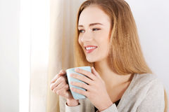Young beautiful woman holding a cup and looking through window. Indoor background Royalty Free Stock Image