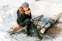 Young beautiful woman holding a Cup of tea outdoors in winter sitting on a log near the fire Royalty Free Stock Images