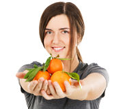Young beautiful woman holding fresh tangerines Stock Photo