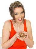Young Beautiful Woman Holding a Handful of Mixed Nuts Royalty Free Stock Photography