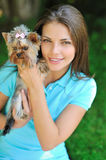 Young beautiful woman holding her puppy dog - outdoor portrait Stock Images