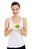 Young beautiful woman holding leaf of lettuce on table. Royalty Free Stock Photography