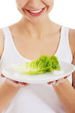 Young beautiful woman holding leaf of lettuce on table. Stock Photo