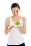 Young beautiful woman holding leaf of lettuce on table. Stock Photography
