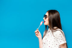 Young beautiful woman holding lollipop isolated on blue background. Happy girl wearing sunglasses eating multi colored. Candy. joyful and cheerful woman eating Stock Images