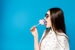 Young beautiful woman holding lollipop isolated on blue background. Happy girl wearing sunglasses eating multi colored. Candy. joyful and cheerful woman eating Royalty Free Stock Photography