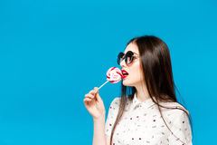 Young beautiful woman holding lollipop isolated on blue background. Happy girl wearing sunglasses eating multi colored. Candy. joyful and cheerful woman eating Royalty Free Stock Photos