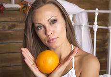 Young beautiful woman holding an orange with two hands. Portrait. Light brown hair Royalty Free Stock Photography