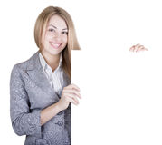 Young beautiful woman holding a place for your advertisement. Royalty Free Stock Image