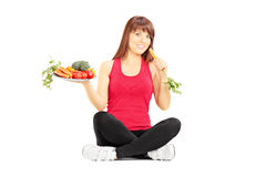 Young beautiful woman holding plate with vegetables and carrots Stock Photography