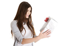 Young beautiful woman holding present with red bow. Royalty Free Stock Photos