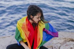 Young beautiful woman holding a rainbow gay flag outdoors. LIFESTYLE an pride concept. love is love