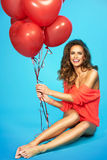 Young beautiful woman holding red balloons on isolated blue background Stock Photo