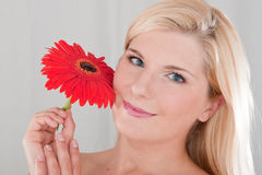 Young beautiful woman holding red flower Stock Photo