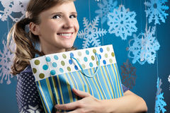 Young beautiful woman holding shopping bag looking at camera smiling. Stock Image