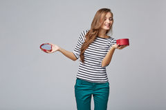 Young beautiful woman holding small red box. Studio portrait on. Gray background Stock Image