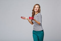 Young beautiful woman holding small red box. Studio portrait on. Gray background Royalty Free Stock Images