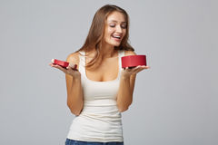 Young beautiful woman holding small red box. Studio portrait on. Gray background Royalty Free Stock Photos