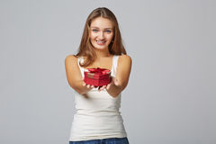 Young beautiful woman holding small red box. Studio portrait on. Gray background Stock Photos