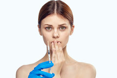 Young beautiful woman holding a syringe on white isolated background, portrait royalty free stock images